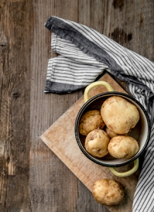 79676688 - young potatoes sitting on cutting board, topview